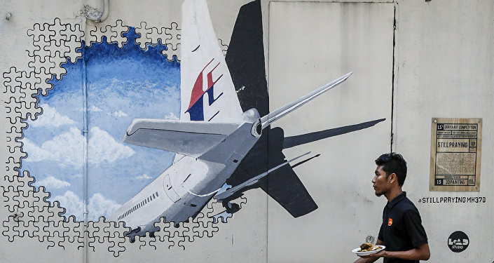 In this Tuesday, Feb. 23, 2016, file photo, a waiter walks past a mural of flight MH370 in Shah Alam outside Kuala Lumpur, Malaysia.