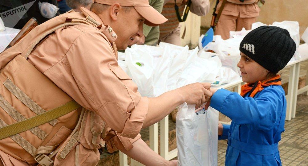 Un militaire russe donne de l'aide humanitaire à un petit habitant d'Alep