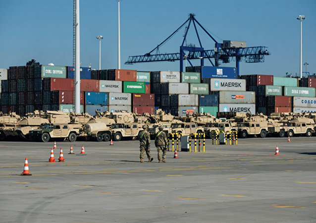 Soldiers walk near U.S. military equipment which arrived as part of NATO mission at port in Gdansk, Poland