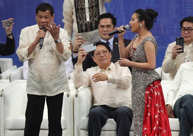 Rodrigo Duterte (L), President of the Philippines, sings a duet with a female singer during a gathering at Lusail Sports Arena in Lusail, 20km north of the Qatari capital on April 15, 2017.