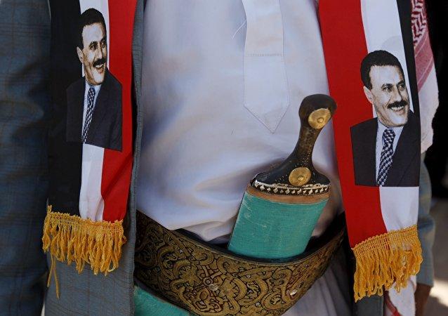 Avec l'image de Saleh sur son écharpe, un homme proteste devant le bureau des Nations unies à Sanaa contre les frappes aériennes menées par l'Arabie saoudite