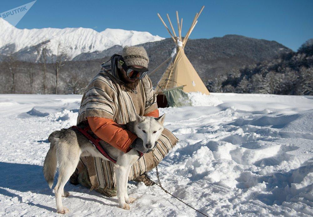 Un maître-chien avec son husky de Sibérie dans l'Husky-camping à la station de ski alpin de Roza-Khoutor, à Krasnaïa Poliana