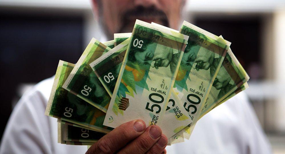 Un employé de banque israélienne tenant des billets de 50 Shekels
