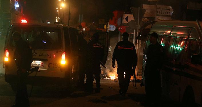 Les véhicules de police devant une barrière de pneus en flammes à Tunis