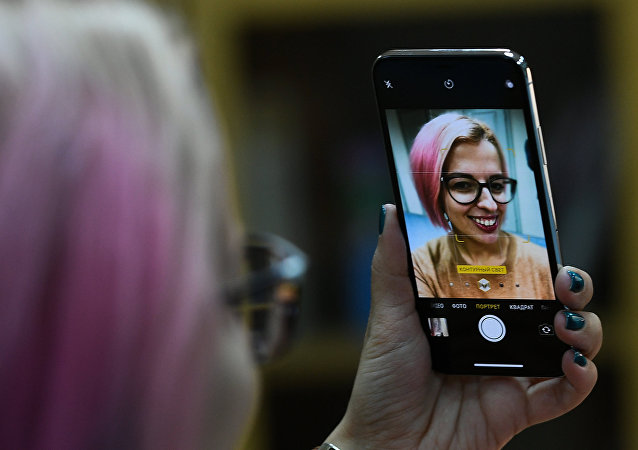 A girl takes a selfie with a new Apple's iPhone X to go on sale in Russia. File photo