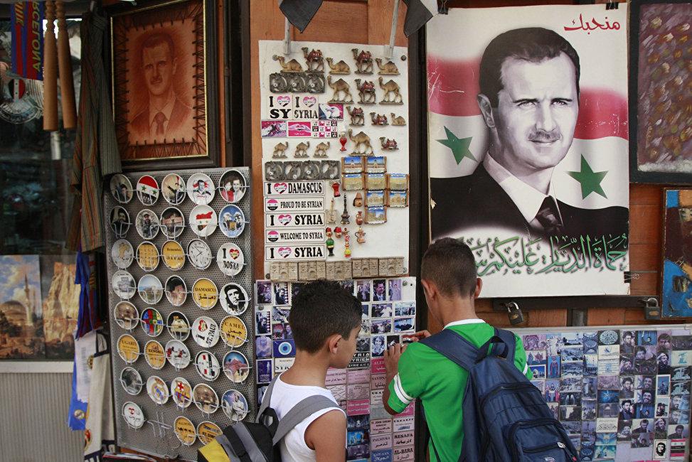 Des écoliers choisissent un souvenir dans un magasin où il y a le portrait de Bachar el-Assad avec la phrase On vous aime marqué dessus, Damas, Syrie