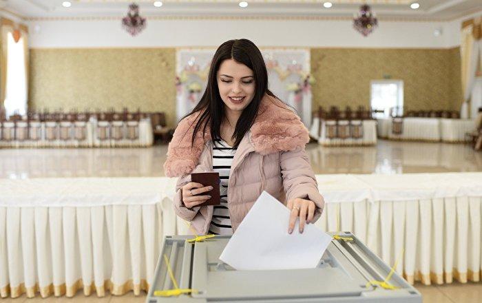 Une jeune femme vote à l'élection présidentielle russe