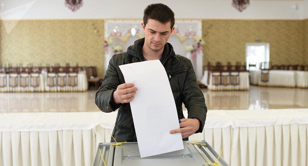 Un jeune glisse son bulletin dans l'urne