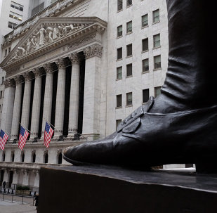 People walk past the New York Stock Exchange (NYSE) on the Wall Street in New York