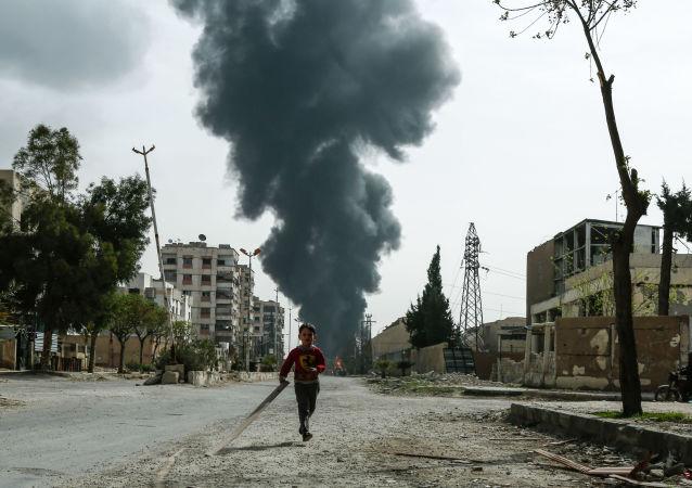 Un enfant dans une rue de Douma après une frappe aérienne