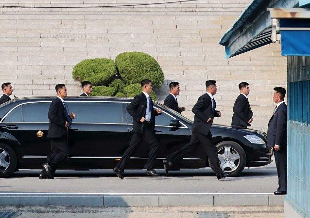 Sécurité au pas de course! 12 gardes du corps de Kim le suivent en courant