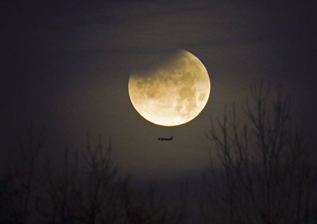 Un avion et la Lune au second plan