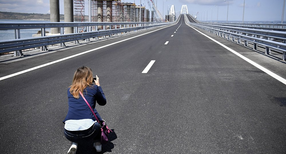 A journalist takes a photograph of the new bridge linking Russia and the Crimean peninsula prior to the opening ceremony near Kerch, Crimea, Tuesday, May 15, 2018