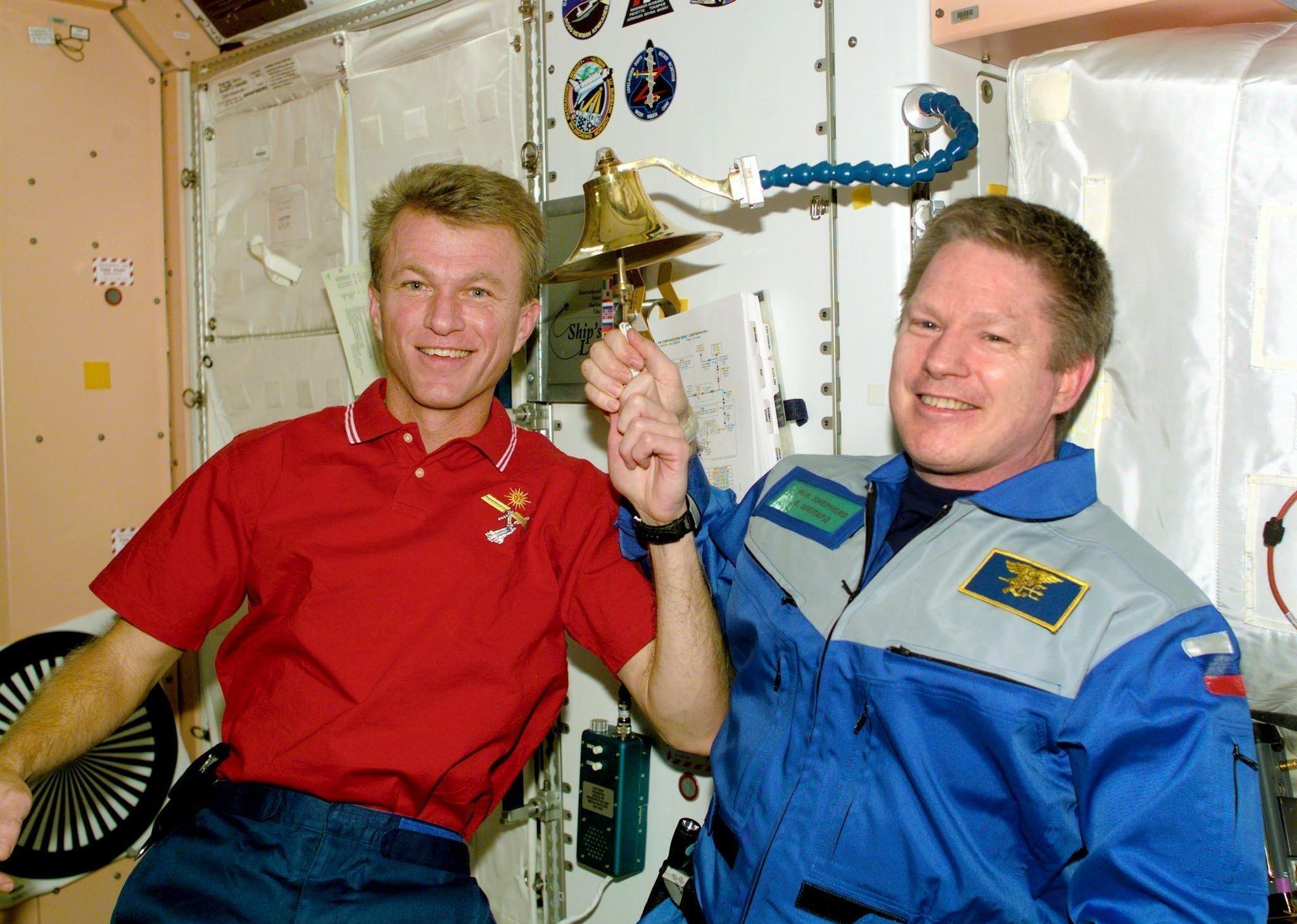 Les astronautes Brent Jett et Bill Shepherd sonnent la cloche de la Station spatiale internationale