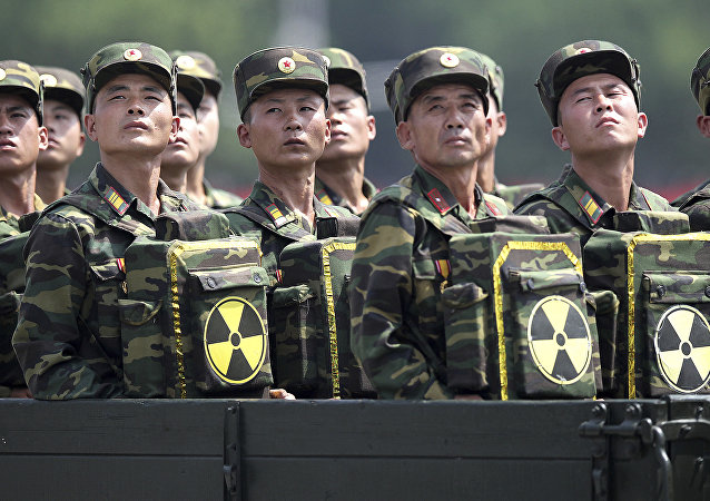 In this July 27, 2013, file photo, North Korean soldiers turn and look towards their leader Kim Jong Un from a military parade vehicle as they carry packs marked with the nuclear symbol during a ceremony marking the 60th anniversary of the Korean War armistice in Pyongyang, North Korea. North Korea has conducted five nuclear tests, the first in 2006. All were conducted in the depths of Mount Mantap, a nondescript granite peak in the remote and heavily forested Hamgyong mountain range about 80 kilometers (50 miles) as the crow flies from Chongjin, the nearest big city. Since North Korea is the only country in the world that still conducts nuclear weapons tests, its Punggye-ri site on _ or mostly under - Mount Mantap is also the world's only active nuclear testing site