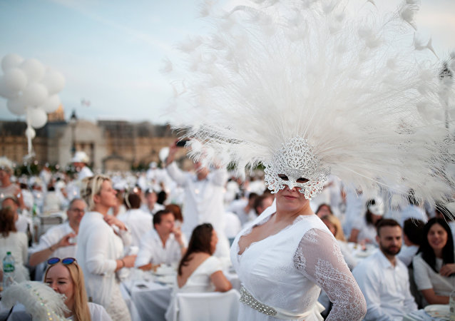 A guest poses near Les Invalides during the Diner en Blanc (Dinner in White) in Paris, France, June 3, 2018. Diners dressed head to toe in white and bringing with them white tablecloths, glassware and other finery, gather for an impromptu open-air dinner, which takes place at a different place in Paris every year. REUTERS/Benoit Tessier