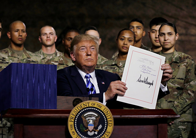 U.S. President Donald Trump holds up the National Defense Authorization Act after signing it in front of soldiers from the U.S. Army's 10th Mountain Division at Fort Drum, New York, U.S., August 13, 2018. REUTERS/Carlos Barria