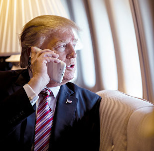 President Donald Trump talks on the phone aboard Air Force One during a flight to Philadelphia, Pennsylvania, to address a joint gathering of House and Senate Republicans, Thursday, January 26, 2017 (File photo).