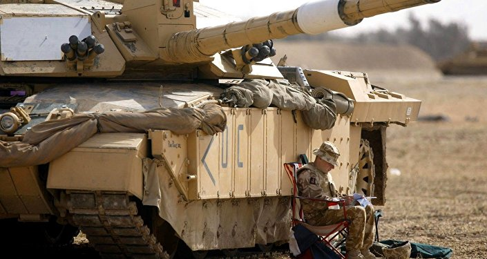 A soldier of the Scots Dragoon Guards sits by a Challenger 2 tank, right, as another sits on top, after being involved in action in Basra, southern Iraq, Saturday 29, 2003