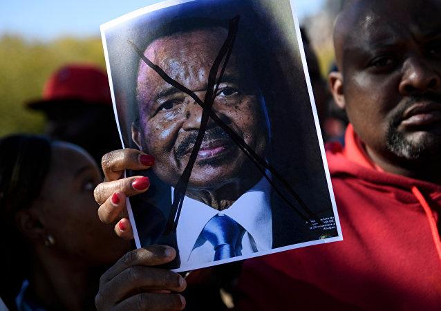 Les gens protestent contre le président camerounais Paul Biya sur l'avenue Pennsylvania, près de la Maison Blanche, le 22 octobre 2018 à Washington, DC.
