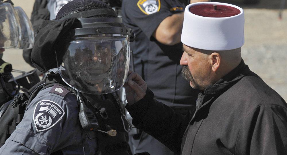 Un membre du communauté druze parle à un membre des forces de sécurité israéliennes lors d'une manifestation contre les élections municipales dans le village de Majdal Chams