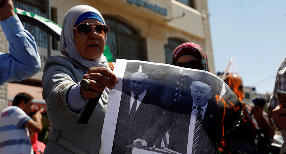 A Palestinian woman burns a picture of U.S. President Donald Trump and Israeli Prime Minister Benjamin Netanyahu during a protest against a U.S. decision to cut funding to the United Nations Relief and Works Agency (UNRWA), in Ramallah, in the occupied West Bank September 4, 2018.