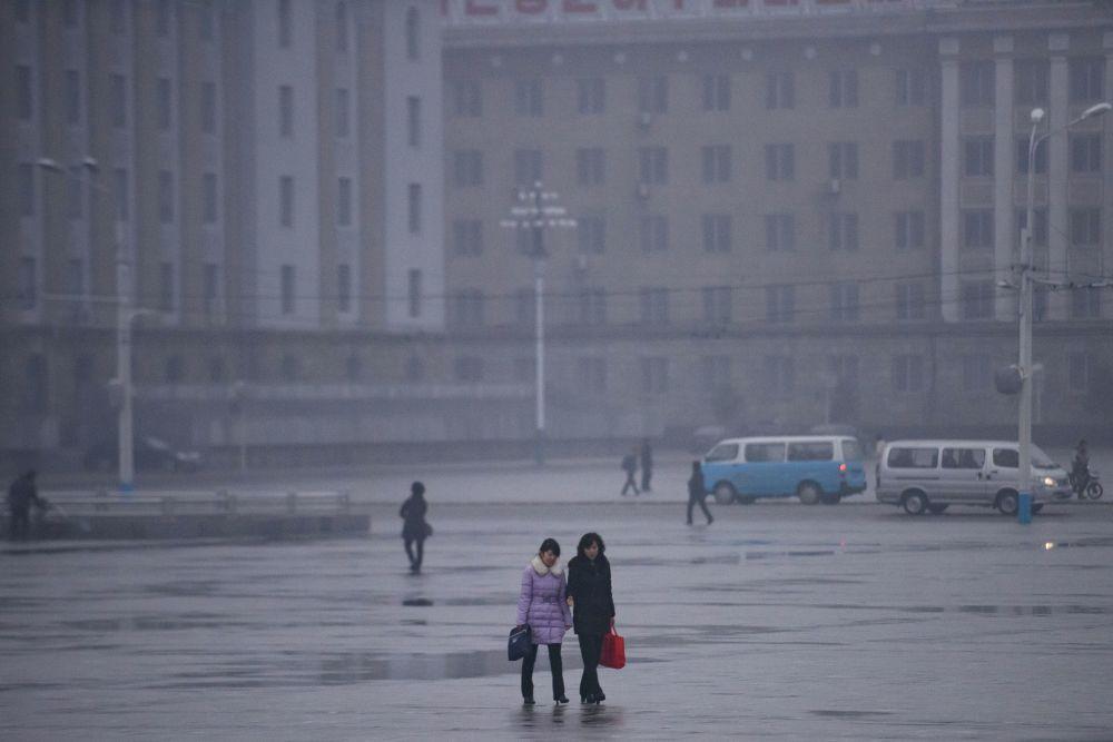 Des passants sur la place Kim Il-sung à Pyongyang, Corée du Nord.