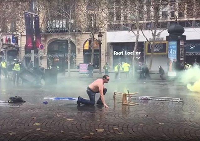 Il enlève son «gilet jaune» pour profiter de la douche devant un canon à eau, 24 novembre 2018