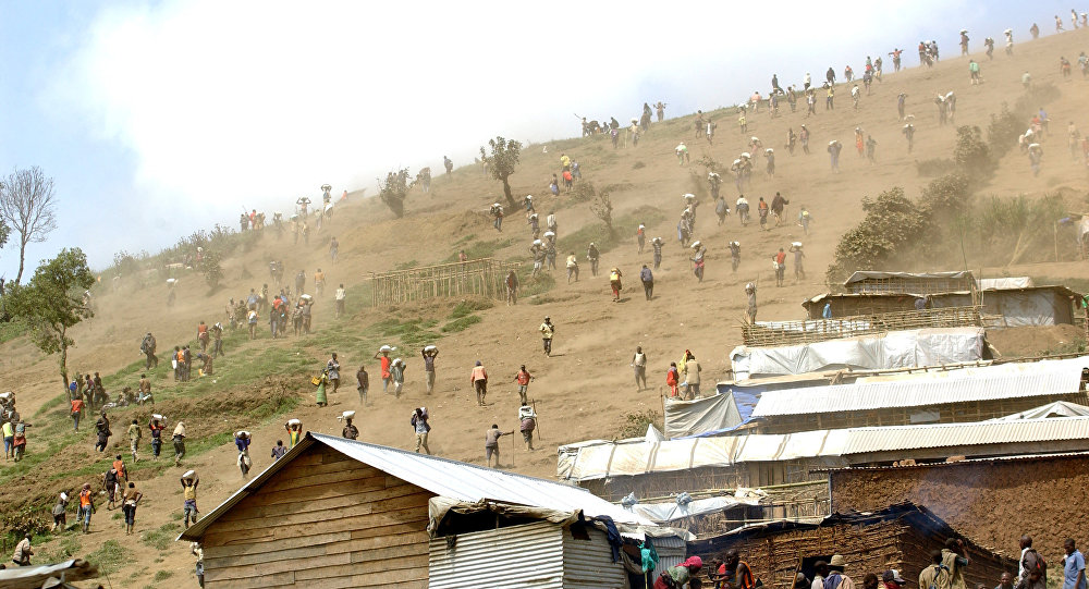 People carry bags of cassiterite (tin ore), coltan, which is used in mobile telephones and computers, and manganese down a hill from the Mudere mine, near Rubaya, some 9 kms from the eastern Democratic Republic of Congo city of Goma (File)