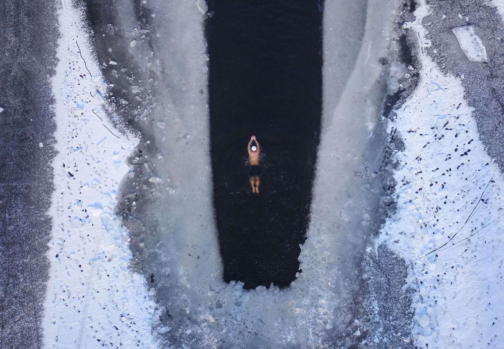 Un homme nage dans un lac partiellement pris de glaces à Shenyang, dans la province chinoise du Liaoning