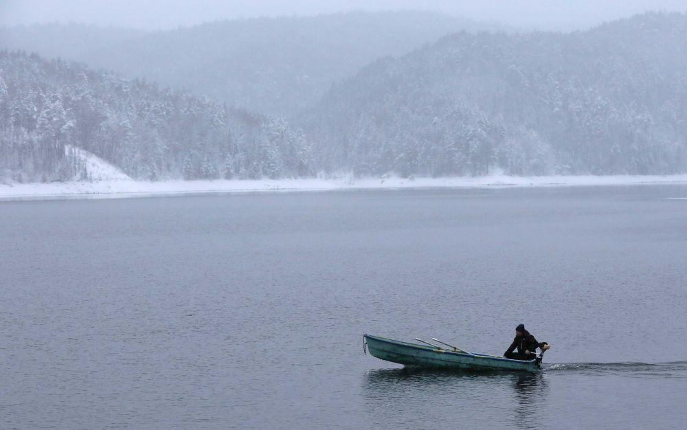 Un homme sur un bateau traverse sous la neige le fleuve Ienisseï près de Krasnoïarsk, en Russie