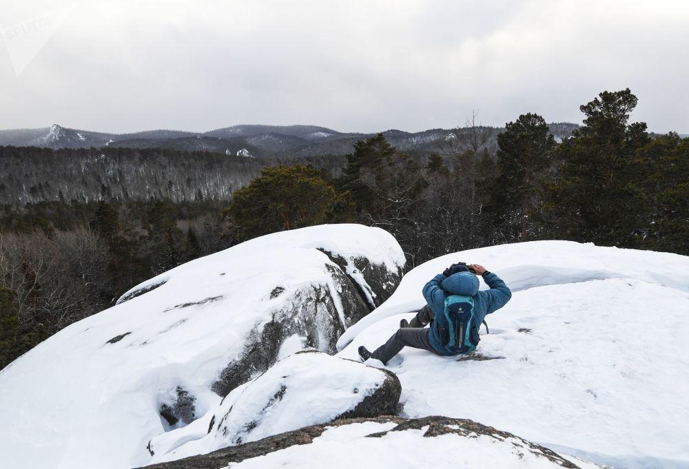 Un touriste sur le rocher du «Quatrième pilier» sur le territoire de la réserve naturelle «Stolby» près de Krasnoïarsk