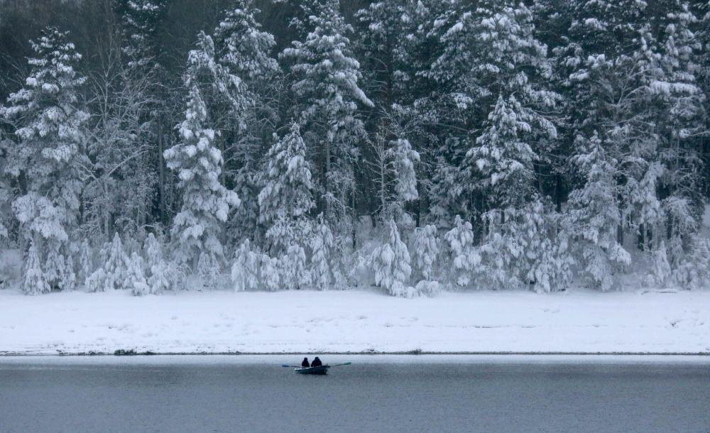 Un bateau traverse sous la neige l'Ienisseï dans la taïga sibérienne près de Krasnoïarsk