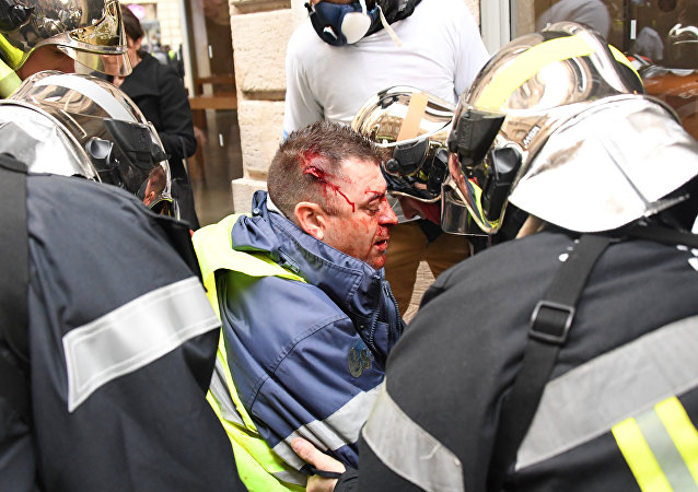 A protester wearing a Yellow Vest (Gilet Jaune) receives first aid after he was injured by a rubber ball shot by a non-lethal hand-held weapon (LBD40) during an anti-government