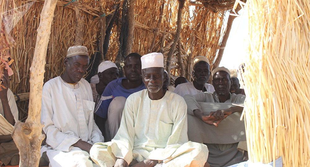 Des hommes assis dans un arbri en matériau provisoire au camp des déplacés de Igawa Mémé, Extrême-Nord, Cameroun