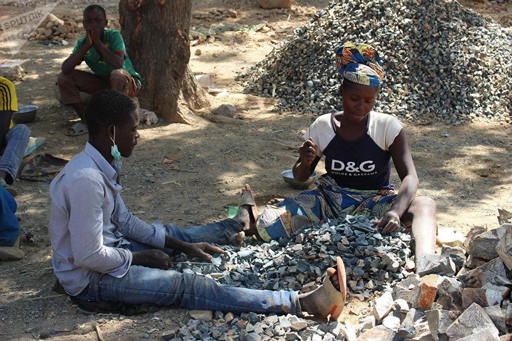 Djamilatou et son frère devant de leur tas de pierres à Maroua, Cameroun
