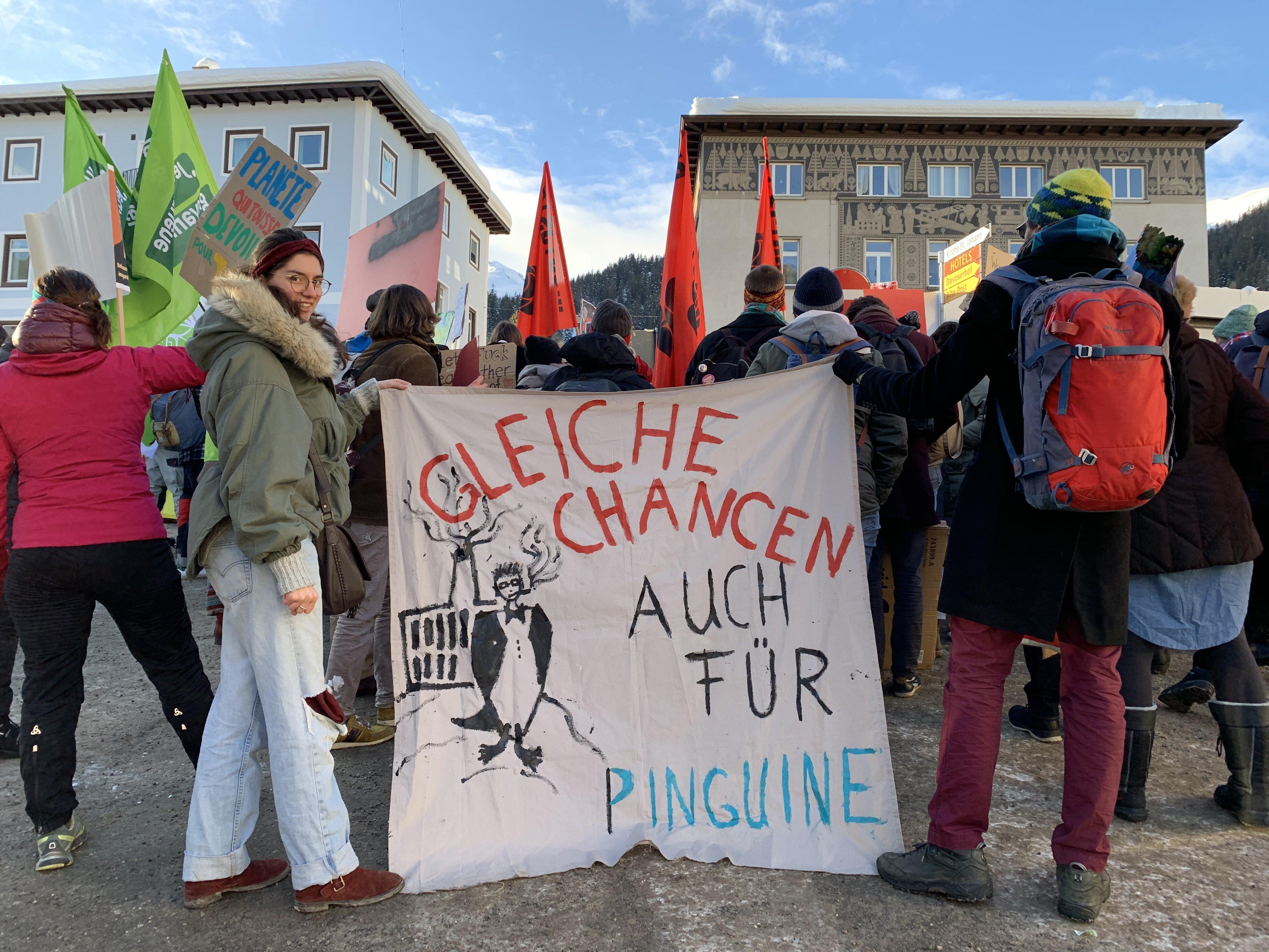 Manifestants à Davos, sur la banderole «égalité des chances, même pour les pingouins.».