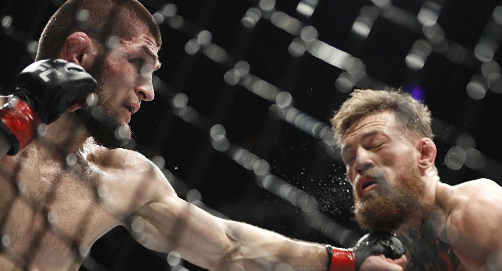 Khabib Nurmagomedov, left, punches Conor McGregor during a lightweight title mixed martial arts bout at UFC 229 in Las Vegas, Saturday, Oct. 6, 2018.