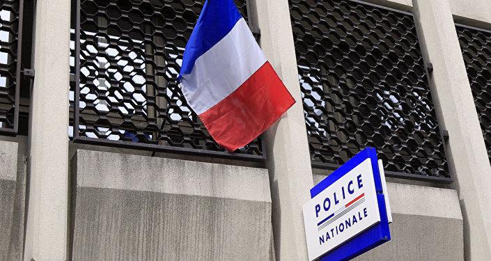 Un drapeau français et l'enseigne de la police nationale