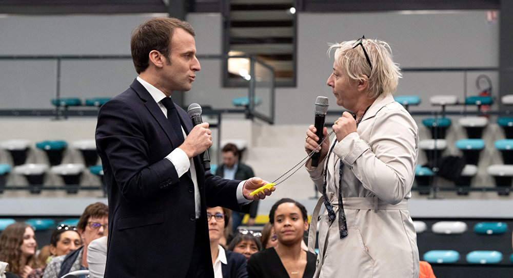 French President Emmanuel Macron (L) speaks with a woman and Yellow Vest activist (R) on February 28, 2019 in Pessac, western France, during a debate with women focused on women social situations.