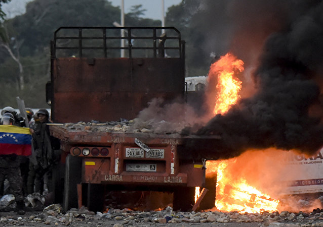 Venezuelan security forces display a national flag next to a truck which was burnt during the weekend when trying to enter the country with humanitarian aid, during clashes with supporters of Venezuelan opposition leader Juan Guaido on the Venezuelan side of the Francisco de Paula Santander International Bridge, as seen from Cucuta, Colombia, on February 25, 2019.