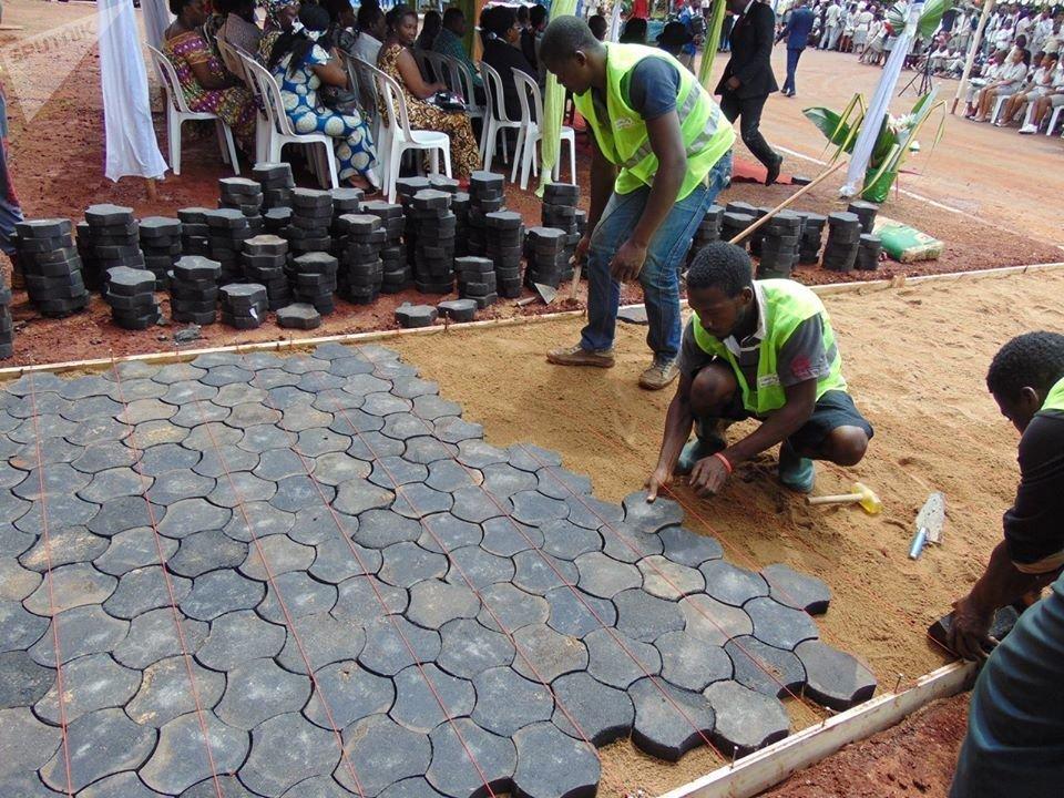 Des jeunes de la fondation Cœur d'Afrique posant des pavés écolos dans un lycée.