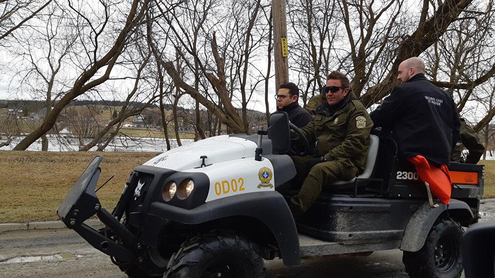 Le député de Beauce-Sud, Samuel Poulin, accompagné d'un agent de la Sûreté du Québec durant la visite d'une zone sinistrée de Sainte-Marie.