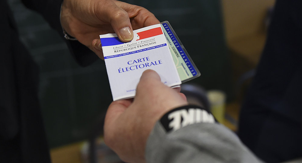 A voter presents his voting documents to a scrutineer at a polling station in Marseille, on May 26, 2019, as part of the vote for the European parliamentary election.