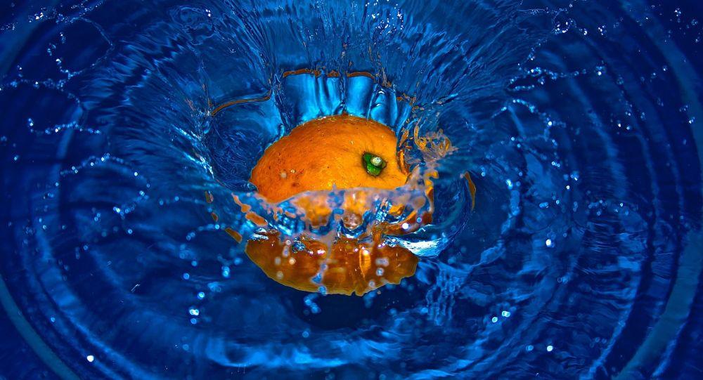 Une orange tombe dans l'eau (image d'illustration)