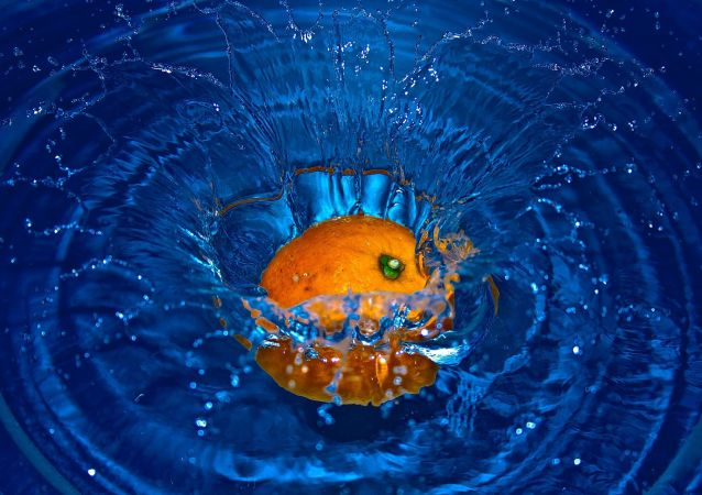 Une orange tombe dans l'eau (image d'illustration)