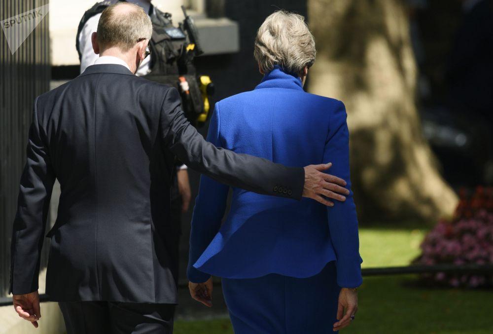 Экс-премьер-министр Великобритании Тереза Мэй покидает резиденцию на Даунинг-стрит, 10 после сложения полномочий. Слева: супруг Т. Мэй Филип Мэй. 24 июля 2019 года в должность премьер-министра  Великобритании вступает лидер Консервативной партии Борис Джонсон.