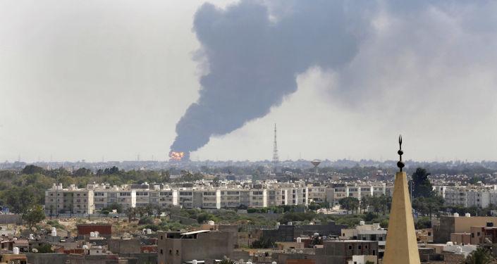 Une fumée noire jaillit sur l'horizon alors qu'un incendie au dépôt pétrolier de l'aéroport déchaînait après avoir été touché par des tirs croisés entre des milices belligérantes se battant pour le contrôle de l'aérodrome de Tripoli.