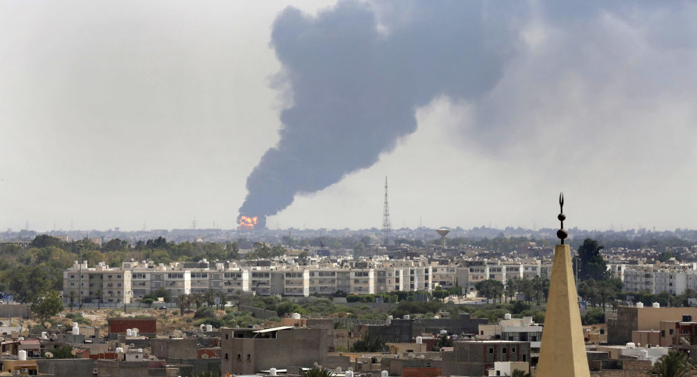 Black smoke billows over the skyline as a fire at the oil depot for the airport rages out of control after being struck in the crossfire of warring militias battling for control of the airfield, in Tripoli,