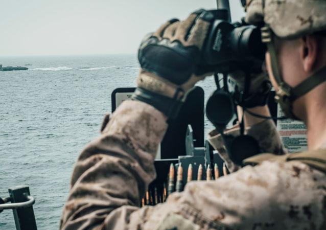 Un militaire américain observe un vaisseau d'attaque rapide iranien du USS John P. Murtha pendant le transit du détroit d'Ormuz, dans la mer d'Oman au large d'Oman